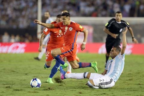 Chilean footballer running past an Argentina player attempting a slide tackle, with another player and referee in the background.